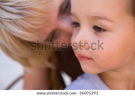 Mam to whisper in son's ear. Focus on child. - stock photo