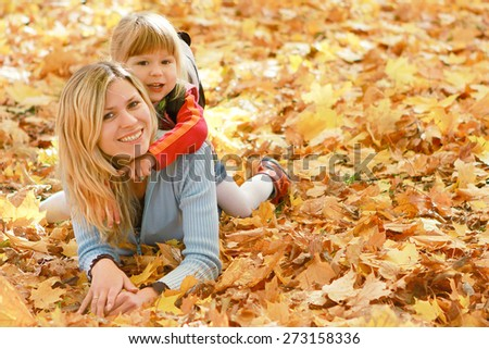 Mama and her little daughter on autumn leaves - stock photo