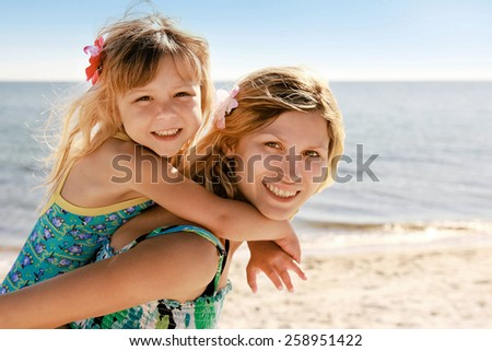 Mama and her little daughter playing on the beach