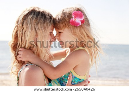 Mama and her little daughter playing on the beach - stock photo