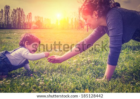 Mama playing with her daughter in a park - stock photo