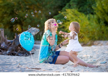 Mama with a small daughter playing on the beach in summer - stock photo