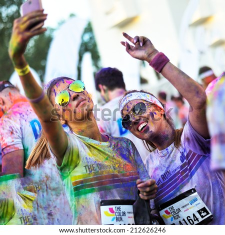 MAMAIA, ROMANIA - JULY 26: Runners take a selfie after The Color Run on July 26, 2014 in Mamaia, Romania. The Color Run is a worldwide hosted fun race with about 1500 competitors in Mamaia - stock photo