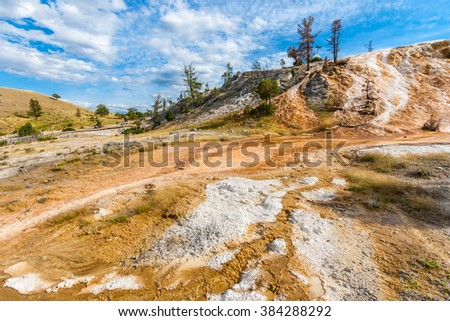 Mammoth Hot Springs in Yellowstone National Park, Wyoming, USA. (Limestone deposited by geothermally-heated water supports colorful thermophiles) - stock photo