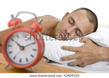 Man a sleep with big red alarm clock in the foreground. The focus is on the man. - stock photo