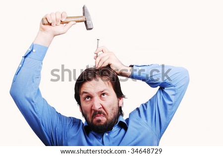 Man about to put nail into his head - stock photo