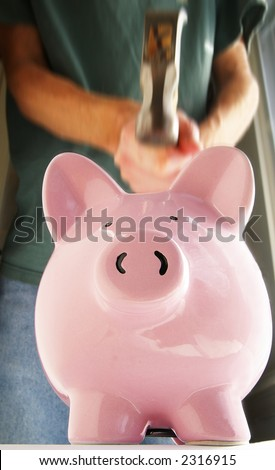 Man about to smash a piggy bank with hammer - stock photo