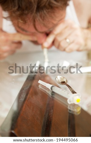 Man abusing cocaine or other powdered drug.  Shallow depth of field with focus on syringe in the foreground.   - stock photo