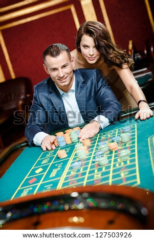 Man accompanied by woman placing bets at the roulette table - stock photo