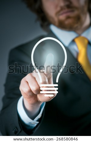 Man activating a light bulb icon on a virtual interface conceptual of a bright idea, inspiration, imagination or innovation in business - stock photo