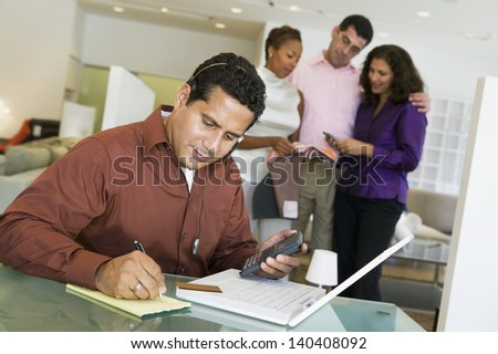Man adding figures with calculator and laptop with salesperson and couple in background at furniture store - stock photo