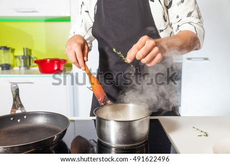Man adding rosemary to meat