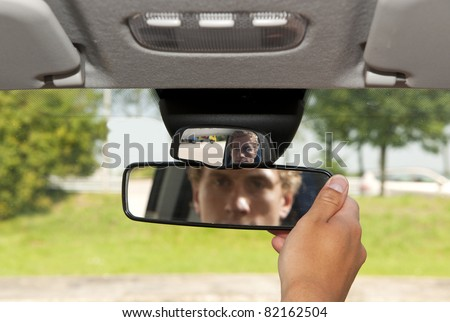 Man, adjusting the rear view mirror of his car - stock photo