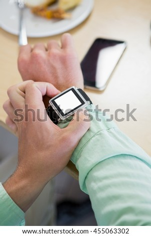 Man adjusting time on his smartwatch in restaurant