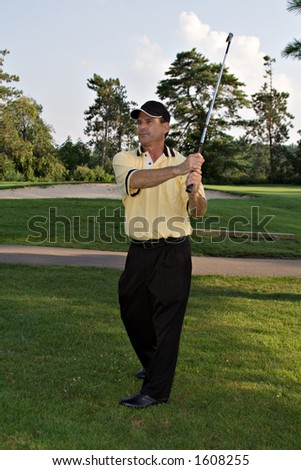 Man after completing a golf swing. - stock photo
