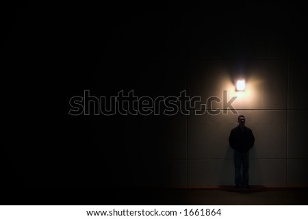 man against a wall and light by a single light - stock photo