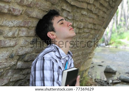Man against wall holding bible to chest with closed eyes - stock photo