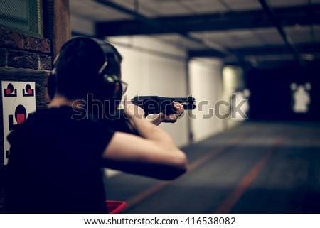 Man aiming shotgun at target in indoor firing range or shooting range - stock photo