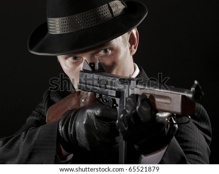 Man aims at submachine gun - stock photo