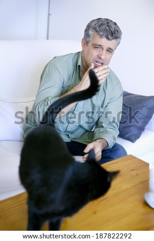 Man allergic to cat  - stock photo