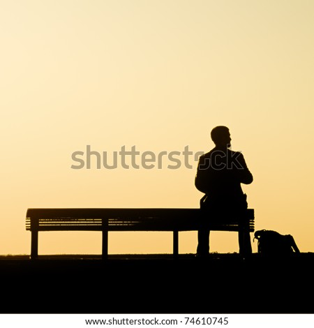 Man alone on bench looks to right