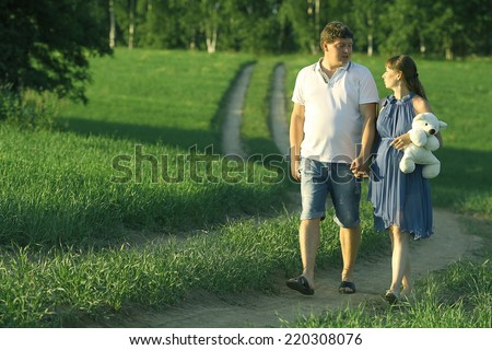 man and a pregnant woman in the field on the road happiness - stock photo