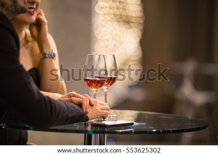 Man and a woman having drinks/glass of wine at a bar (shallow DOF; color toned image)