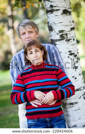 Man and a woman of middle age standing in the park with his back to a tree - stock photo