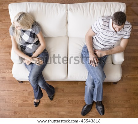 Man and a woman sit distantly on the ends of a cream colored love seat. Horizontal shot.