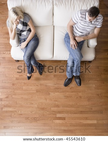 Man and a woman sit distantly on the ends of a cream colored love seat. Vertical shot. - stock photo