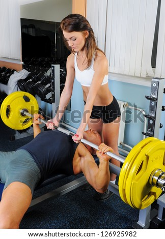 man and a woman trained in the gym Bar Bench Press - stock photo
