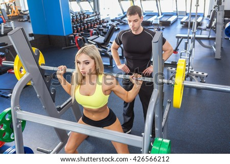 man and blonde woman with barbell flexing muscles in gym. woman and personal trainer in gym - stock photo