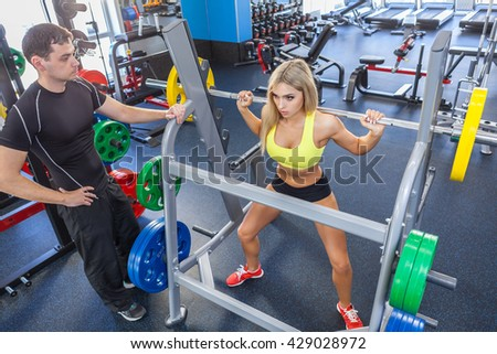 man and blonde woman with barbell training muscles in gym. woman and personal trainer in gym - stock photo