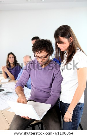 Man and businesswomen in front of laptop computer - stock photo