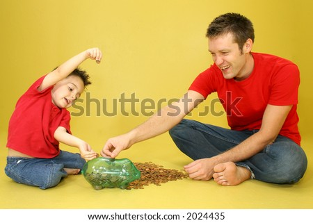Man and child putting pennies in piggy bank. - stock photo