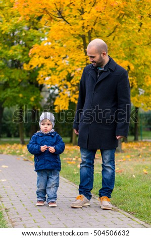 Man and child walking on a footpath at a park on a autumn day