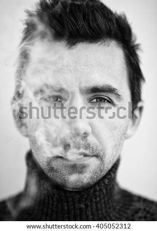 Man and cigarette smoke. Portrait. Closeup. Black and white photography. - stock photo