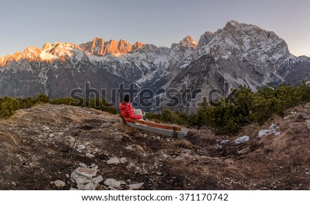 Man and dog resting at the top of the hill and observing the sunset in the mountains. - stock photo