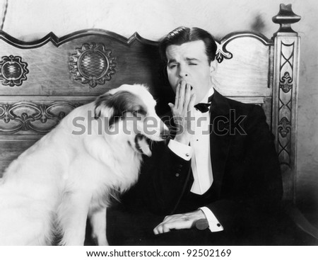 Man and dog sitting together yawning - stock photo