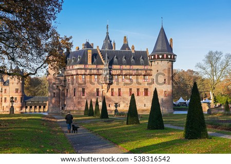 Man and dog walking in the park near the medieval castle  De Haar  in autumn, The Netherlands