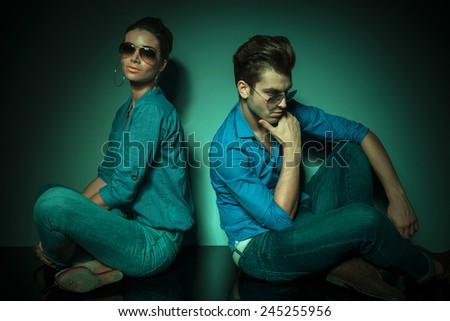 Man and fashion woman sitting back to back on studio background. she is looking at the camera while he is looking down thinking. - stock photo