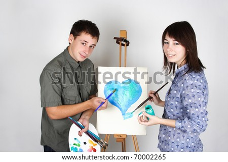 man and girl holding brushes and palette, painting blue heart - stock photo