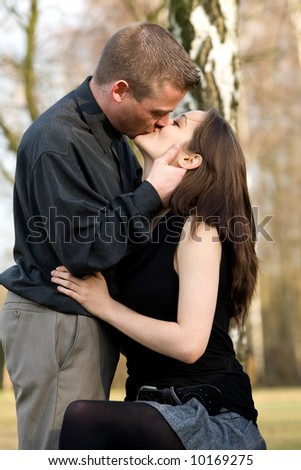 Man and girlfriend on a bench in a park kissing