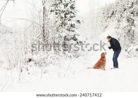 Man and golden retriever outdoors  in the trees and snow snow - stock photo
