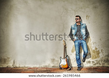 man and guitar against a grungy wall. Processed for hdr tone mapping effect - stock photo