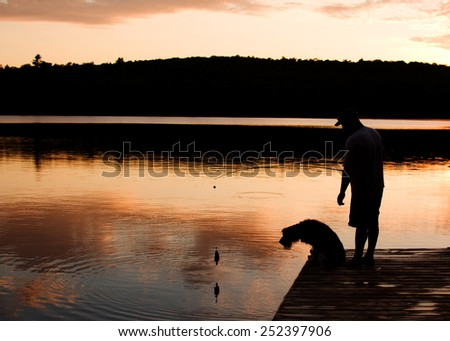 man and his dog fishing at sunset from a dock - stock photo
