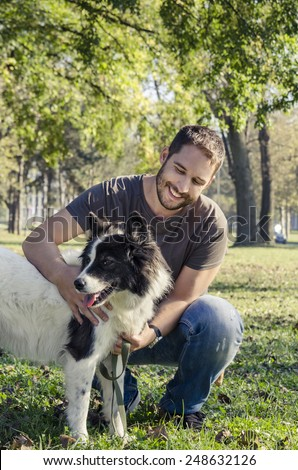Man and his dog playing in the park - stock photo