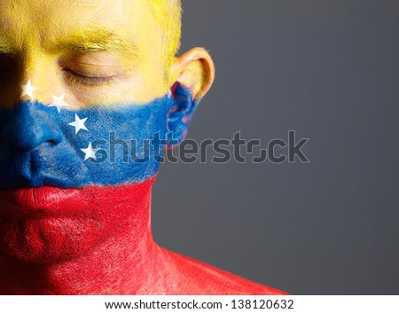 Man and his face painted with the flag of Venezuela. The man has his eyes closed and photographic composition leaves only half of the face. - stock photo