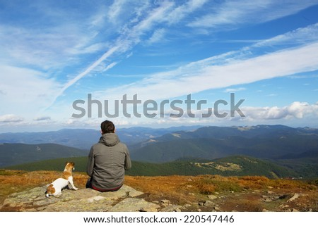 Man and his faithful friend the dog admire the mountain scenery in the campaign - stock photo