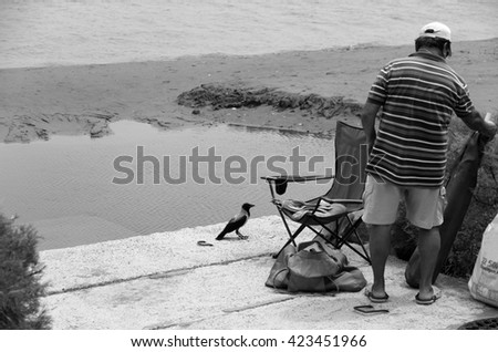 Man and his feathered friend packing up after a days fishing - stock photo